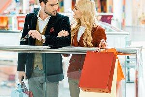 young stylish couple holding shoppin