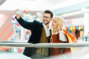 young excited couple with shopping b