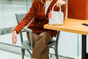 smiling blonde girl sitting in mall