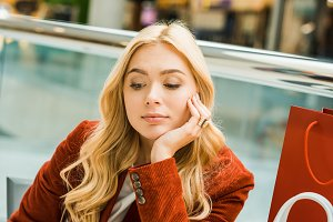upset blonde girl sitting in mall wi