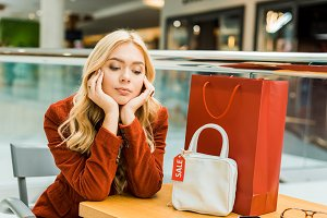 upset woman sitting in mall with one