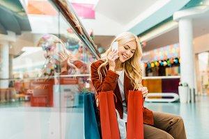 smiling shopaholic talking on smartp
