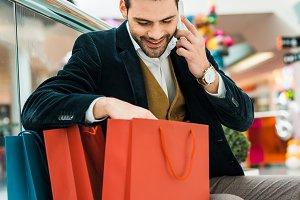stylish man looking into shopping ba