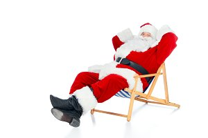 happy santa claus relaxing on beach