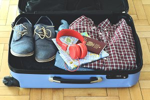 Packed suitcase of vacation items