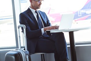 adult businessman in glasses typing