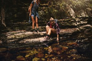 Female hikers by a water pond