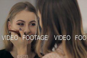 A professional makeup artist puts on
