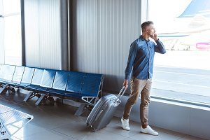 Handsome man with silver luggage tal