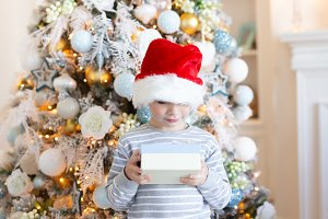 Boy in santa hat with gift box over