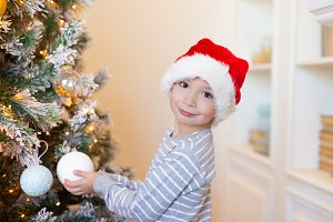 Boy in santa hat decorating
