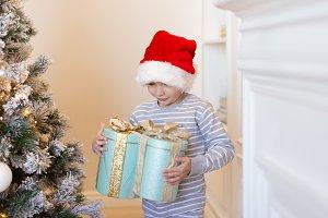 Boy in santa hat holding gifts near