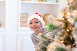 Boy in santa looks out from