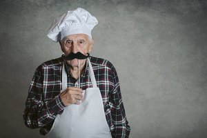 funny senior man with cook hat