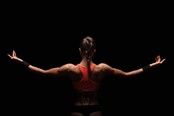 Athletic young woman showing muscle…