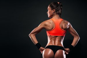 Athletic young woman showing muscles