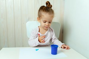 Beautiful little girl draws with fin