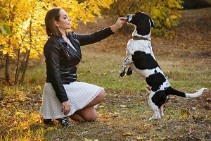 Girl and dog in autumn park