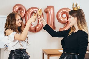 Two business women raise glasses in
