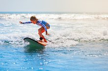 Young surfer rides on surfboard
