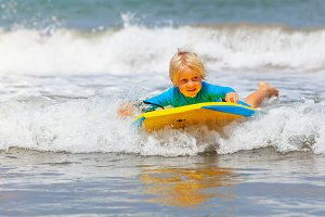 Little child swimming with bodyboard