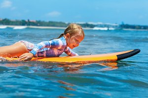Young surfer paddle on surfboard