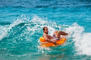 Funny man riding on tubing on wave