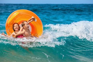 Happy kids have fun in sea surf