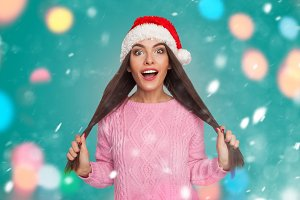 Model holding hair in christmas hat