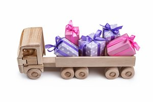 Wooden toy car with gifts in boxes