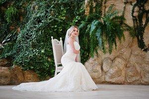 Gorgeous blonde bride sitting on cha