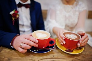 Newlyweds sitting on table at cafe w