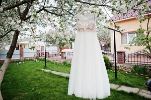 Wedding white dress hanging on the b
