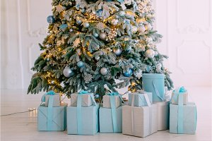 Christmas gifts in boxes under tree