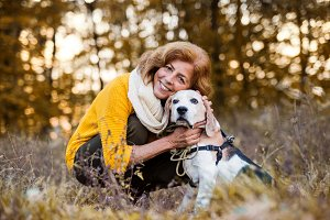 A senior woman with a dog in an