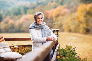 An elderly woman standing outdoors