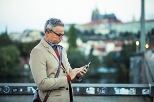 Businessman with smartphone standing