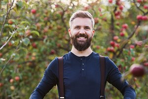 A mature man standing in orchard in