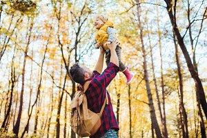 A mature father lifting a toddler