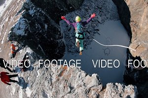 A man jumps off a cliff. Rope