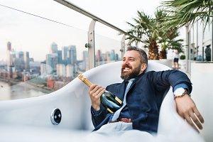 Businessman lying in empty hot tub