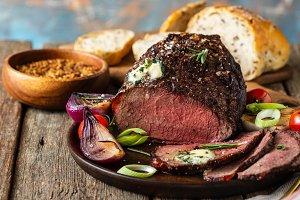 Roast beef on cutting board. Wooden