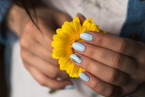 blue manicure holds a yellow flower