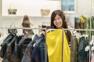 Happy Asian woman choosing clothes a