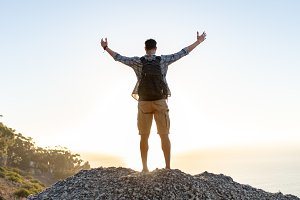 Hiker with arms outstretched on hill