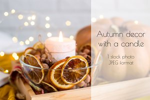 Burning candle in autumn decor