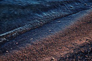 Small waves wash up along a sandy be