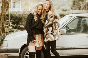 Models Laughing By Old Car