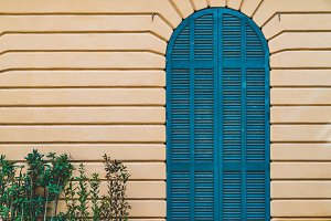 Arched door in blue on a yellow wall