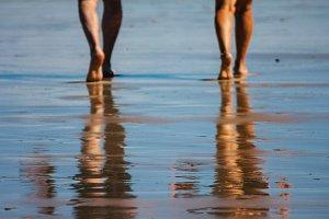 Legs of people walking in a beach